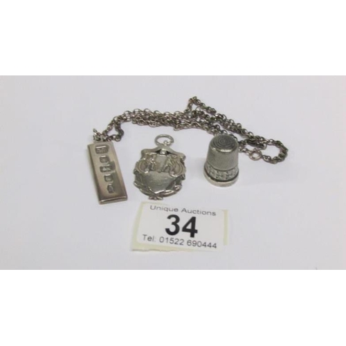 34 - A silver ingot HM Sheffield 1977, A silver fob HM Birmingham 1921/22 and a silver thimble (HM worn)...