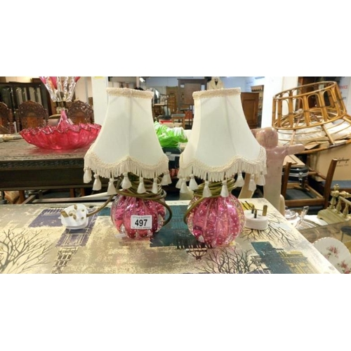 497 - A pair of cranberry glass lamps with shades...