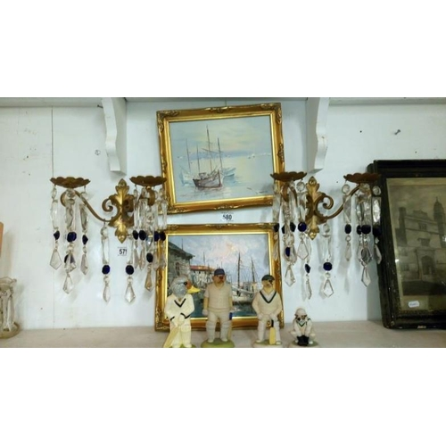 579 - A pair of gilded wrought iron double wall candle holders with glass droppers...