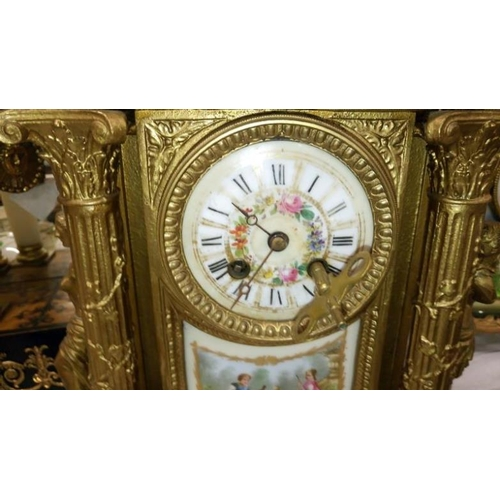 625 - A gilded mantel clock with enamelled dial, porcelain panel and surmounted figures...