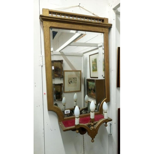 666 - A gilded wall mirror with attached lights...