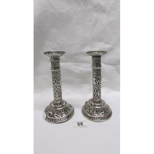 68 - A pair of ornate Indian silver candlesticks...