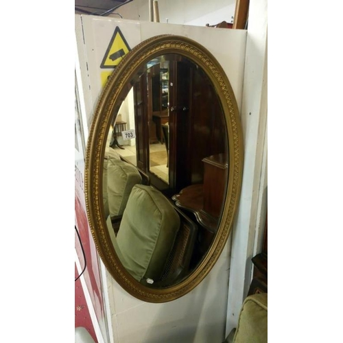 703 - A Victorian/Edwardian oval gilt framed bevel edged mirror...
