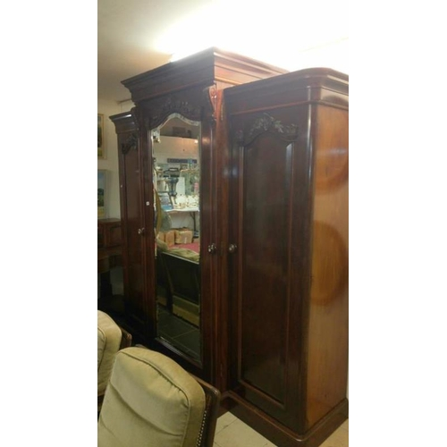708 - A Victorian mahogany triple wardrobe with central mirror door...