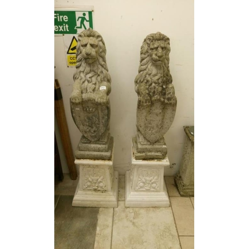 717 - A pair of garden lions on pedestals and holding shields...