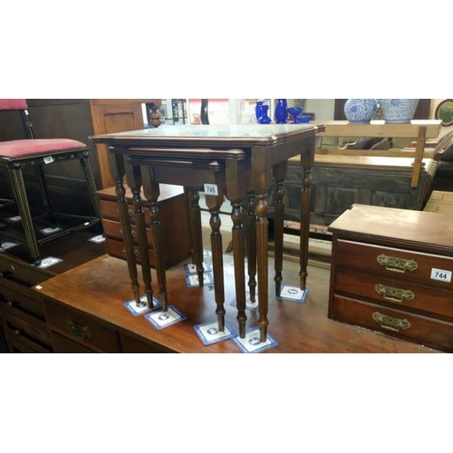 745 - A nest of 3 dark wood table with glass tops and green/gold leather insets...