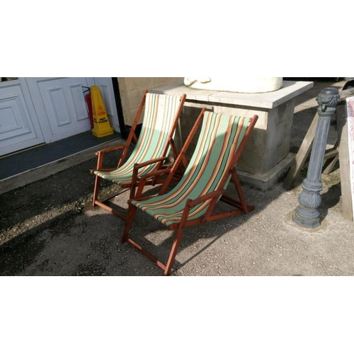 751 - A pair of vintage hard wood deck chairs with arms...