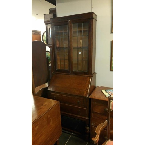 757 - A 1930's oak bureau bookcase with leaded glass doors...
