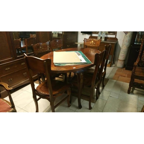 763 - An oval dining table and 6 chairs with brass inlay...