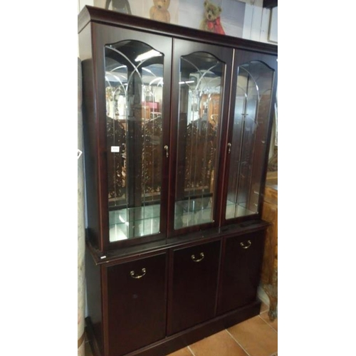 771 - A modern dark wood stained display cabinet with cut glass doors and mirror back...