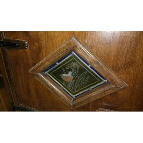 778 - A continental oak kitchen cupboard with stained glass panel in door and tiled top...