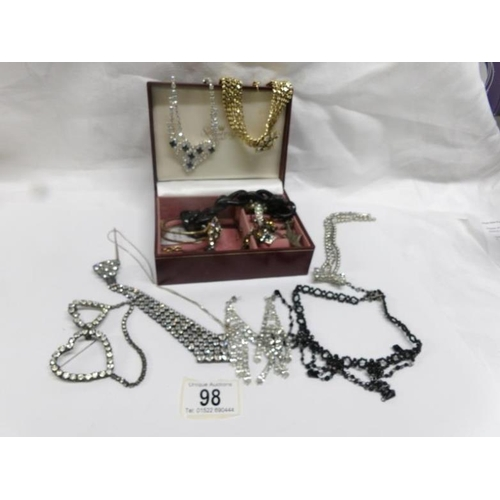 98 - A jewellery box and contents including necklaces, brooches etc...