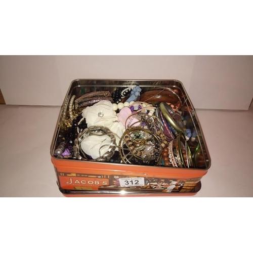 312 - A tin of costume jewellery...