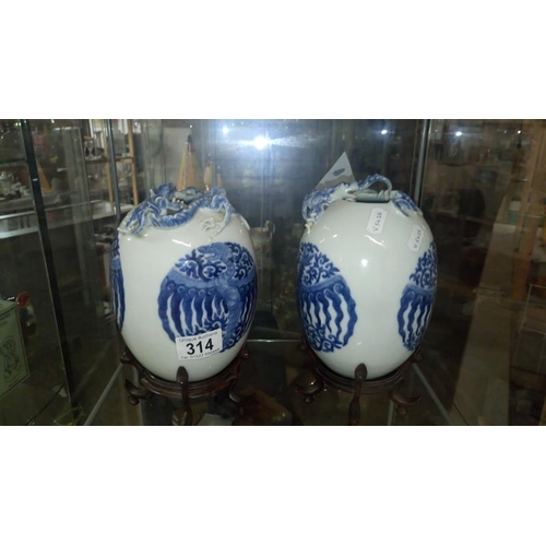 314 - A pair of Chinese blue and white vases on stands and with dragon features...