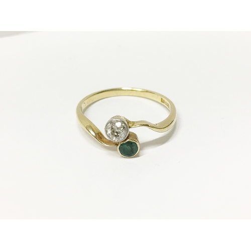 15 - An 18ct gold diamond and emerald cross over ring, size 0...