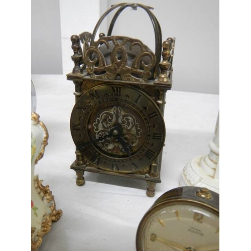 509 - A small lot of assorted mantel clocks including brass lantern clock (bell present but not fitted)....