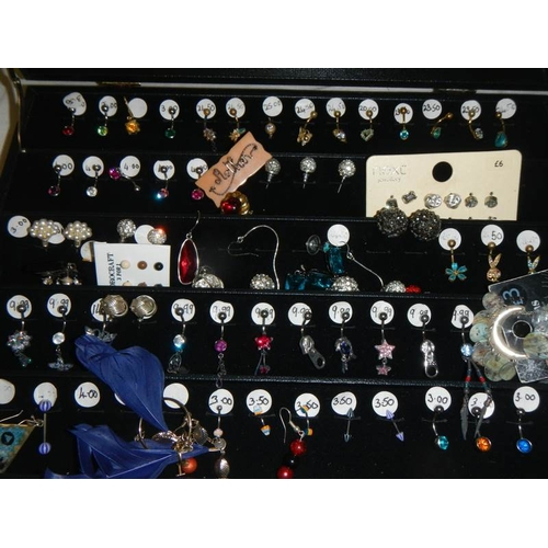 526 - A cabinet of pairs and single earrings....