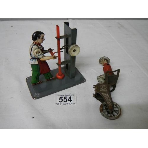 554 - A tin plate steam hammer figure and a Llehman coach driver....