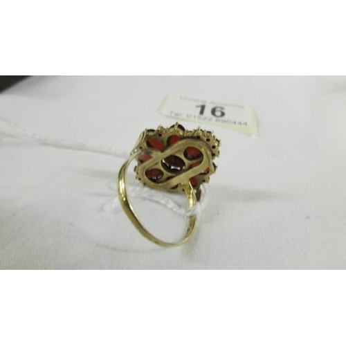 16 - A 9ct gold ring set garnets, size T....