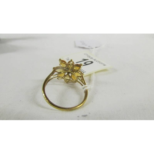 19 - A 9ct gold ring in a floral design, size U....