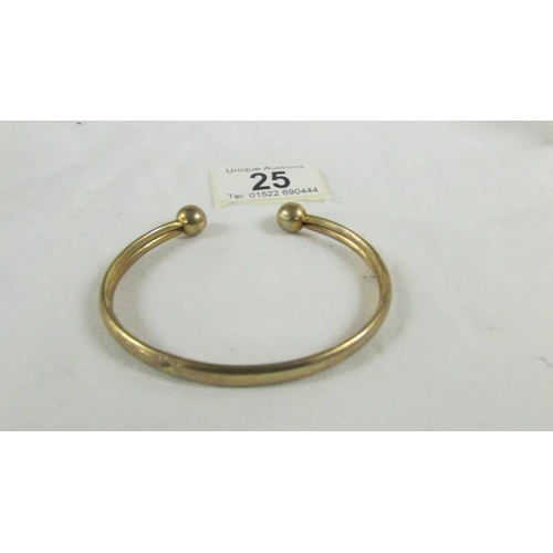 25 - A 9ct gold bangle, 9.5 grams.  (small dint)....