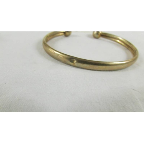 25 - A 9ct gold bangle, 9.5 grams.  (small dint).