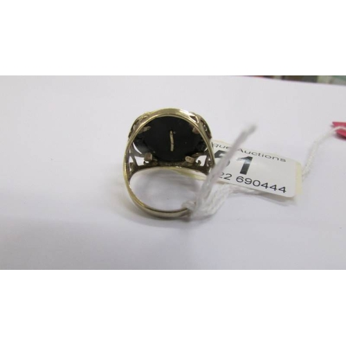 51 - A gentleman's 9ct gold ring with a gold eagle inserted into an onyx base, gold open work shoulders, ...