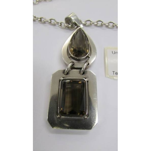 55 - A quality smoky quartz heavy silver pendant and chain with attached heart charm.  Total weight 80 gr...