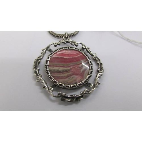 56 - A fancy silver open work pendant with attached silver chain and set with pink/grey banded agate, cir...