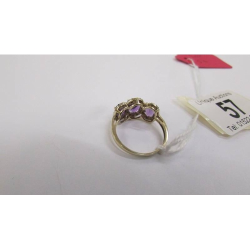 57 - A 3 stone diamond and amethyst ring in a cluster style, deep colour amethyst in a gold tested shank....