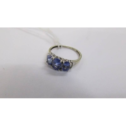 58 - A three stone baguette diamond and tanzanite ring in white gold, size P....