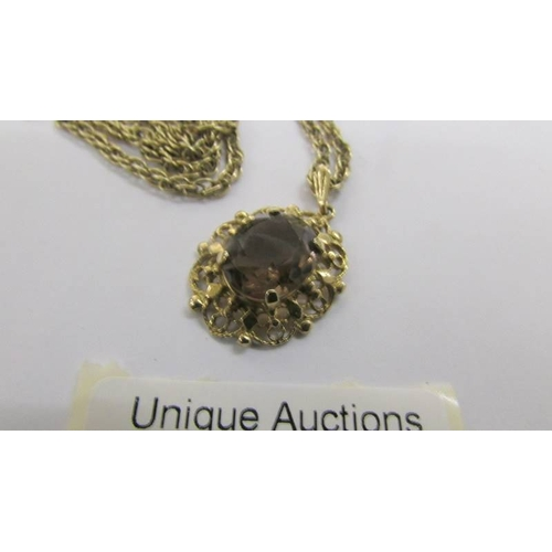 59 - A fancy gold work pendant set with 9 smoky quartz in oval mount with attached 9ct gold chain, total ...