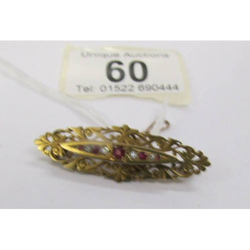 60 - An antique ruby and diamond brooch in 15 carat hall marked gold with attached safety chain....