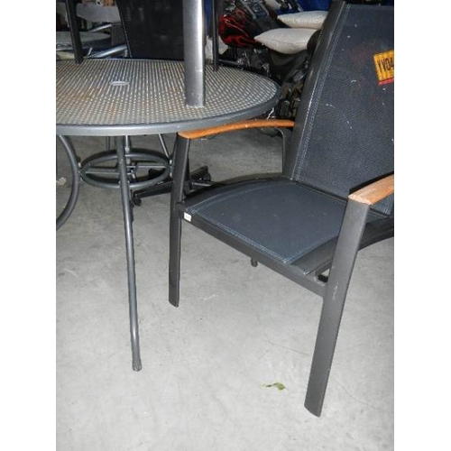 350 - A circular garden table and 2 metal and mesh framed garden chair with teak arms.