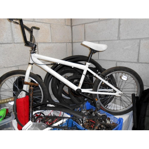 24 - A large quantity of used bicycle parts including gears, levers, lights, seats, plus a bike and wheel...