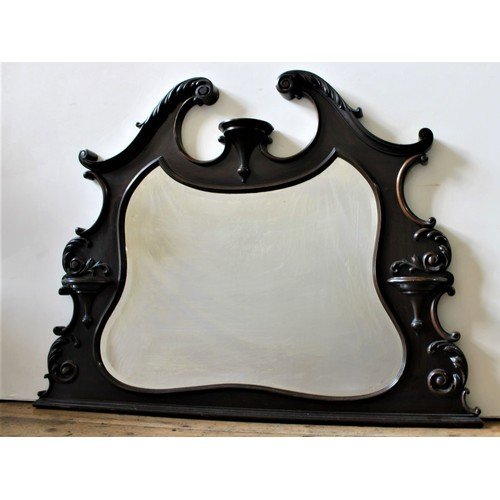 11 - AN ORNATE CARVED FRAMED OVERMANTEL MIRROR, the bevelled mirror contained within an ornate scroll wor...