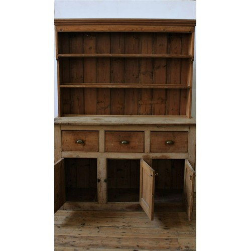 12 - A RUSTIC PINE THREE DOOR KITCHEN DRESSER WITH 3-TIER PLATE RACK, the base comprised of three deep dr...