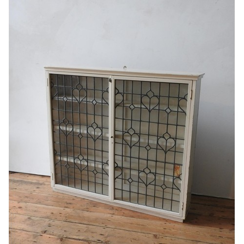 18 - A CREAM PAINTED LEADED LIGHT TWO DOOR BOOKCASE, with three interior shelves, 113 x 126 x 24cm