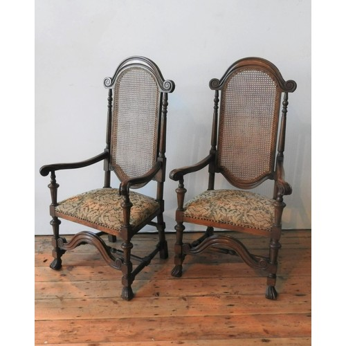 35 - A PAIR OF 17th CENTURY STYLE OAK CANE PANEL BACK CHAIRS, with scroll arms, claw feet and ornate stre...