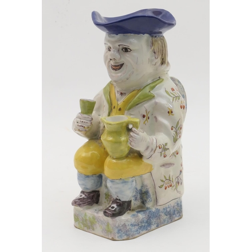 4 - French faience toby jug, in the style of Quimper, traditionally modelled and decorated with yellow w...