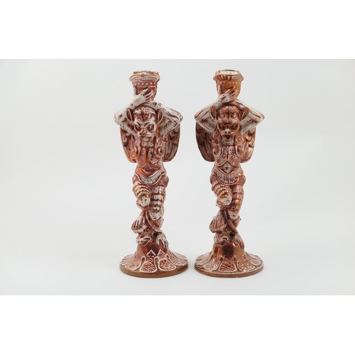 56 - Matched pair of Cantagalli figural candlesticks, in the Hispano Moresque style, modelled as winged b...