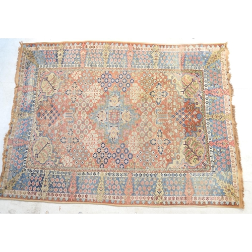 579 - Persian Heriz woollen carpet, faded red field dispersed with floral clusters within a sky blue borde...