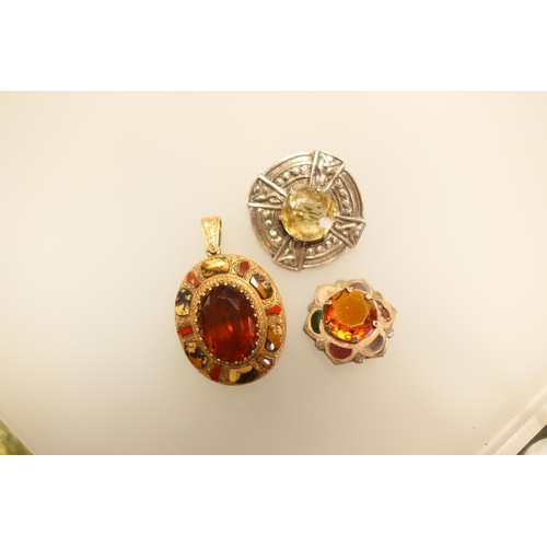 340 - Scottish agate gold plated oval locket and two Scottish themed silver brooches centred with gem ston...
