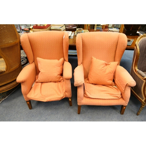643 - Pair of traditional salmon pink upholstered wing armchairs...