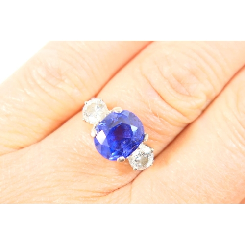 209 - Tanzanite and diamond three stone ring, the oval cut stone of approx. 2cts, 9mm x 8mm, in a four cla...