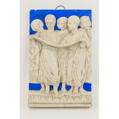 23 - Continental relief moulded pottery panel, modelled with choristers and decorated in white and blue g...