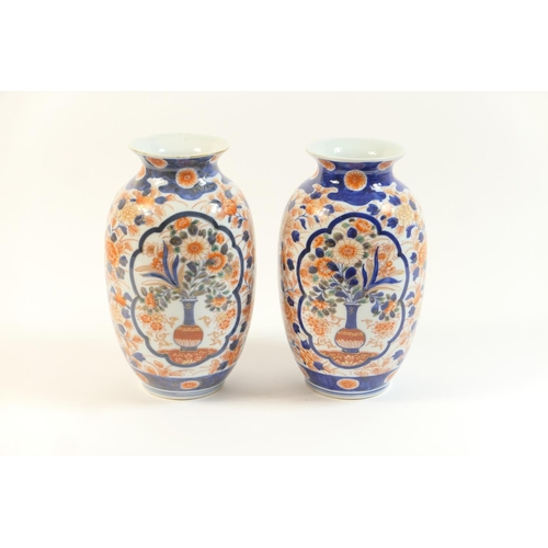 24 - Pair of Japanese Imari vases, Meiji (1868-1912), decorated in typical palette with flowering vase pa...
