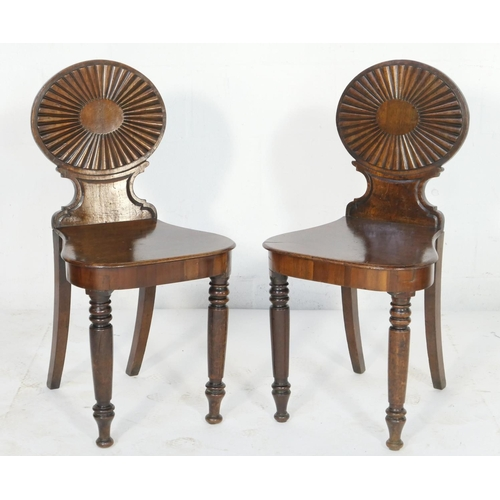 676 - Pair of late George III mahogany hall chairs after Ince & Mayhew, each having an oval reeded fan bac...