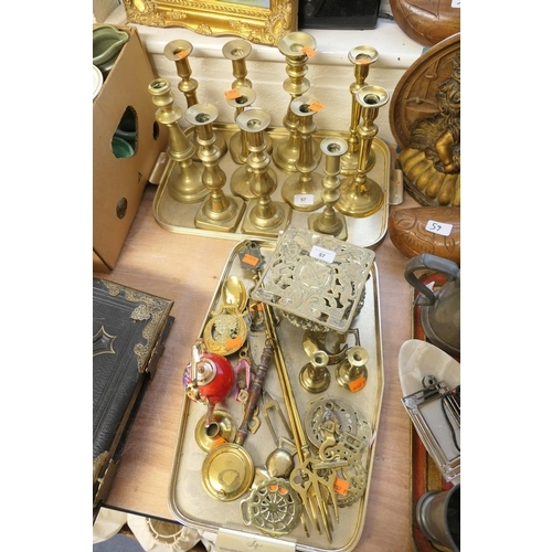 57 - Six pairs of brass candlesticks, also horse brasses, teapot stand etc (2 trays)...