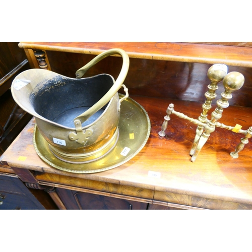 710 - Brass fire dogs, coal scuttle and decorative plaque...